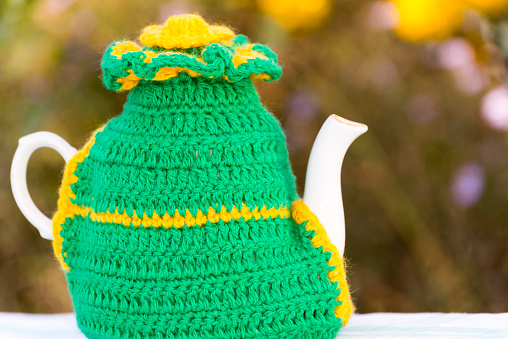 Knitted doily on the teapot on  natural backgroun