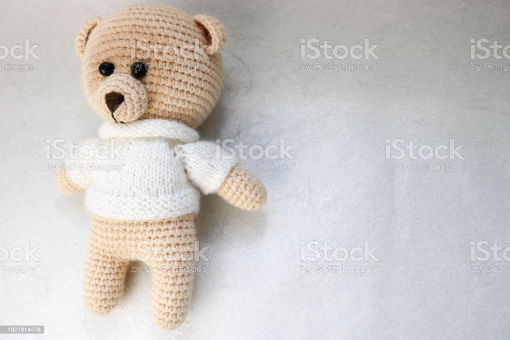Un punto casera hermosa lindo osito en un suéter blanco con ojos negros, un juguete de peluche atado con hilos grandes color beiges sobre un fondo blanco claro. El fondo - foto de stock