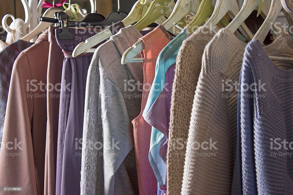 Knitted homemade clothes of different colors hanging in the store stock photo