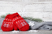 Knitted mittens with gray scarf and fir tree branches on white wooden background