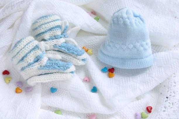 gestrickte neugeborenes baby booties und hut auf gehäkelte decke weißen hintergrund mit bunten herzen - jungendecken häkeln stock-fotos und bilder