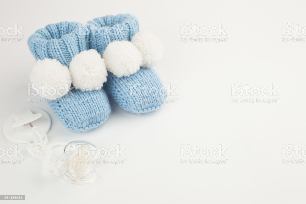 knitted newborn baby booties and soother on white background with copy space zbiór zdjęć royalty-free
