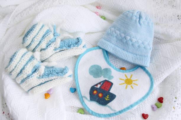 neugeborenes baby booties, hut und lätzchen auf gehäkelte decke weißen hintergrund mit bunten herzen gestrickt - jungendecken häkeln stock-fotos und bilder
