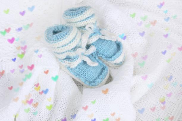 neugeborenes baby booties auf gehäkelte decke weißen hintergrund mit bunten herzen gestrickt - jungendecken häkeln stock-fotos und bilder