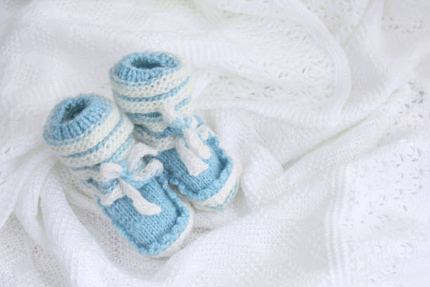 neugeborenes baby booties auf gehäkelte decke weißen hintergrund gestrickt - jungendecken häkeln stock-fotos und bilder