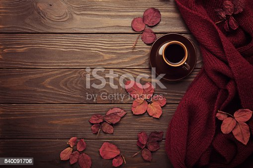 istock Knitted scarf of burgundy color with autumn leaves and a cup of coffee on a dark wooden background. 840091706
