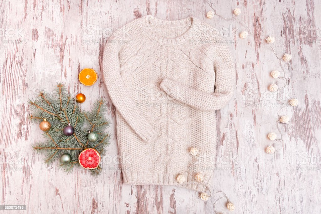 Knitted sweater, a decorated fir branch and a garland on a wooden background. Fashionable concept. stock photo