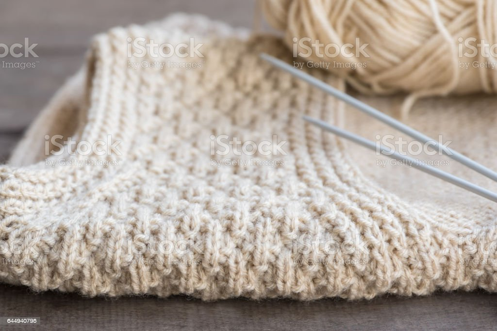 Knitted sweater with knitting needles and yarn. stock photo