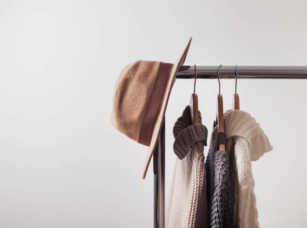 Knitted sweaters on hangers and felt hat stock photo