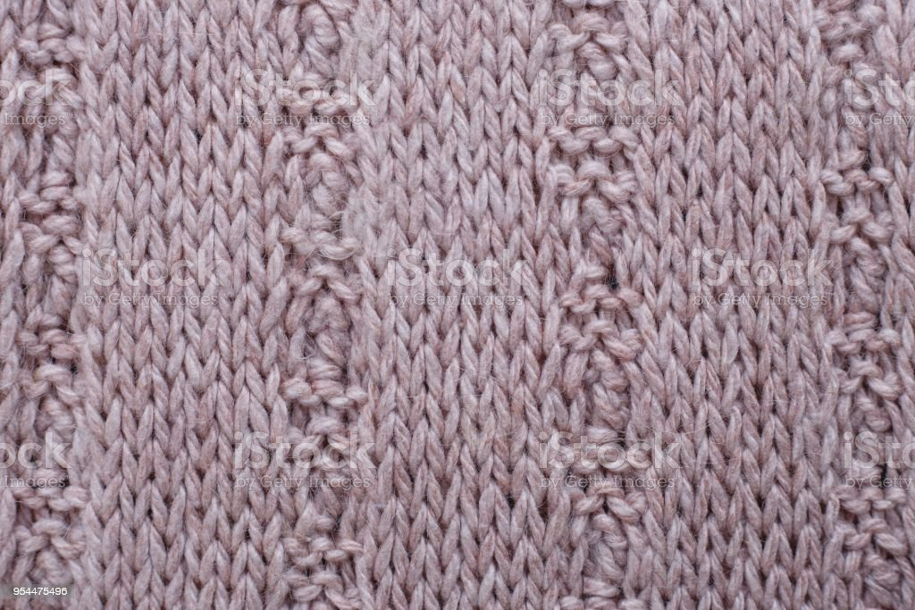 Knitted texture of beige woolen fabric with pattern. Copyspace,