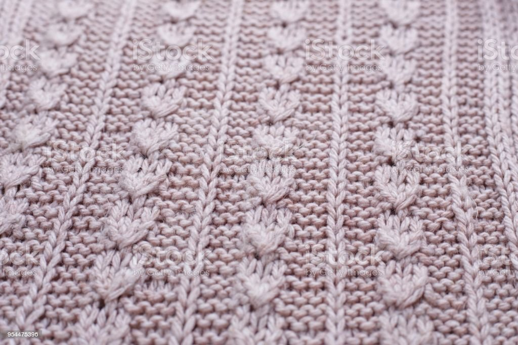 Knitted texture of beige woolen fabric with pattern, selective f