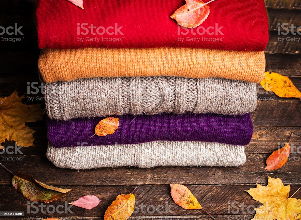 Knitted winter clothes on wooden background covered with autumn leaves. stock photo