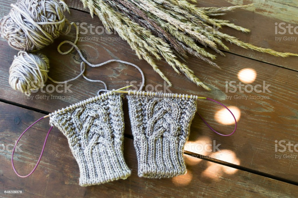 Knitted wool cloth and needles on wooden table stock photo