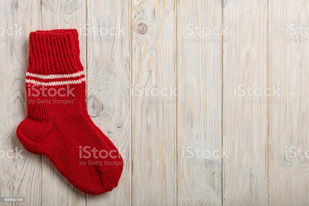 Knitted wool socks red color on light wooden background. stock photo
