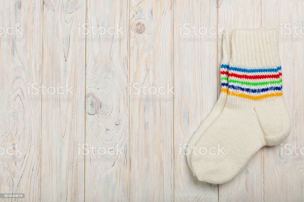 Knitted wool socks white color on bright wooden background. stock photo