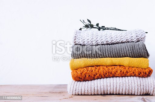 Pile of knitted woolen sweaters autumn colors on wooden table. Clothes with different knitting patterns folded in stack. Warm cozy winter fall knitwear concept. Copy space.