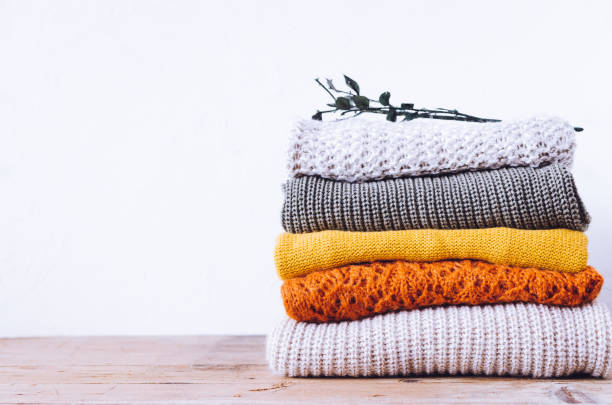 Knitted wool sweaters Pile of knitted woolen sweaters autumn colors on wooden table. Clothes with different knitting patterns folded in stack. Warm cozy winter fall knitwear concept. Copy space. clothing stock pictures, royalty-free photos & images