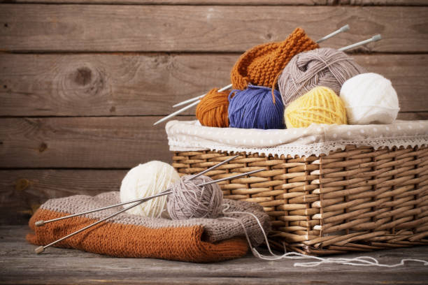 Knitting and knitting needles on a wooden surface stock photo
