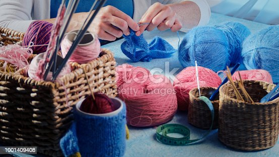 Woman is knitting at the home desk. Colorful balls of wool and knitting needles on the foreground. Pink and blue colours