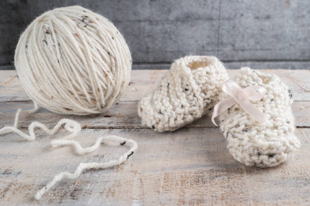 stricken baby booties mit bege garn auf holztisch - babyschuhe nähen stock-fotos und bilder