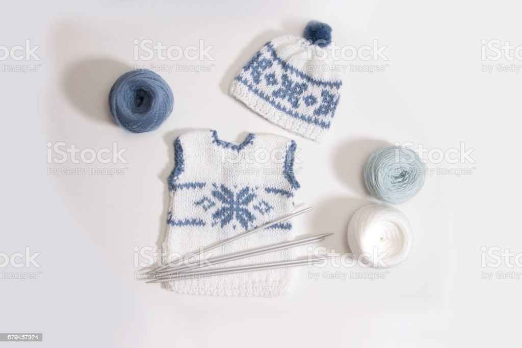 knitting clothes for the newborn on a white background. needles and yarn for knitting royalty-free stock photo