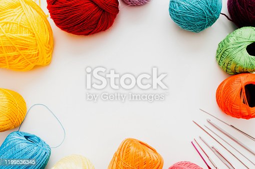 Knitting course. Creative hobby leisure. Multicolor threads crochet hooks on white background.