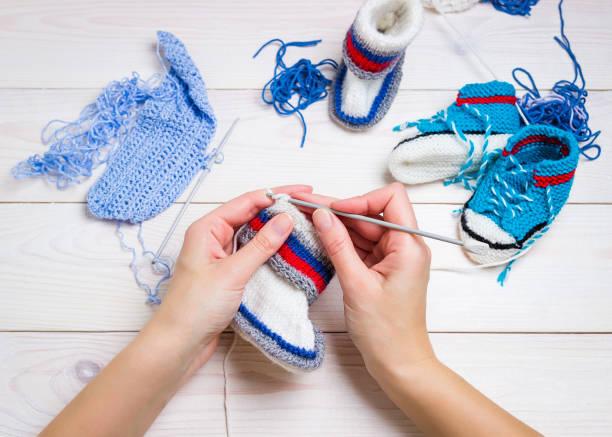 stricken. hand-häkeln.  weibliche hand stricken haken. - babyschuhe nähen stock-fotos und bilder