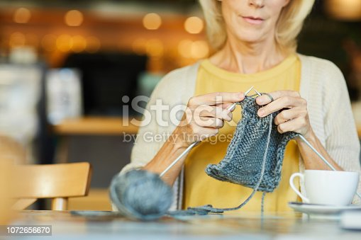 Mature female sitting by table and knitting warm woolen knitwear by cup of tea