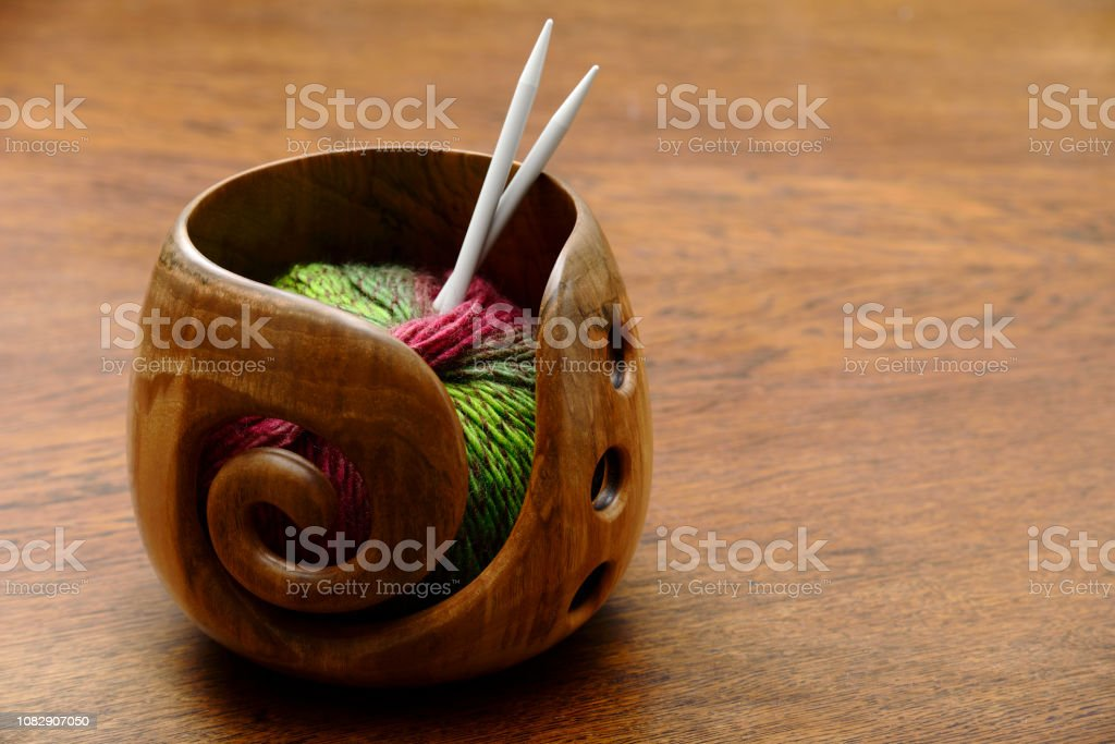 knitting needles and wool in a wooden handmade bowl stock photo