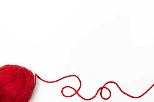 Red ball of wool is on the white.