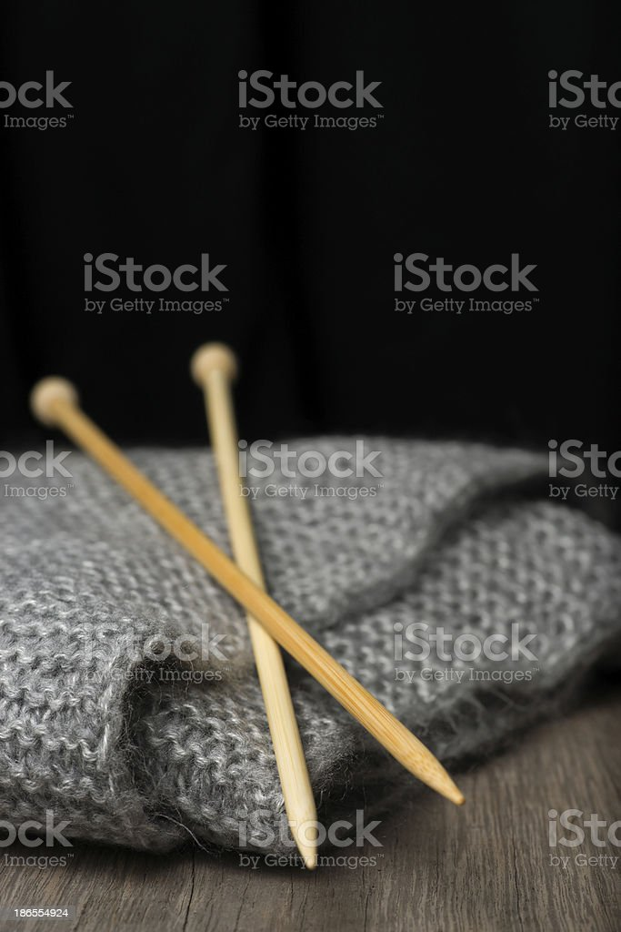 Knitting sticks and crey wool blanket on wooden table. royalty-free stock photo