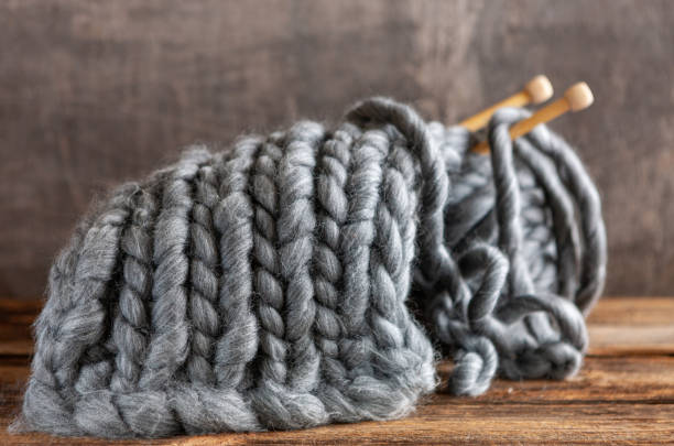 Tricô. Fios cinzentos grossos em agulhas de tricô de madeira. Clew e tela, textura. - foto de acervo