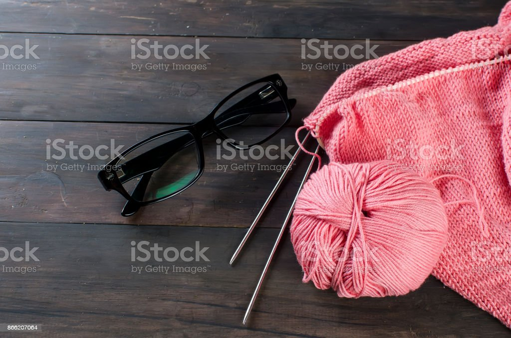 knitting threads and glasses  on a wooden table. stock photo