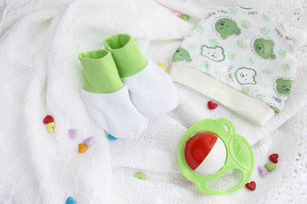 strickwaren neugeborenes baby booties und hut mit bunten rassel auf gehäkelte decke weißen hintergrund mit bunten herzen - jungendecken häkeln stock-fotos und bilder