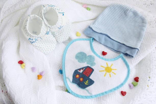 strickwaren neugeborenes baby booties, mütze, lätzchen auf gehäkelte decke weißer hintergrund mit bunten herzen - jungendecken häkeln stock-fotos und bilder