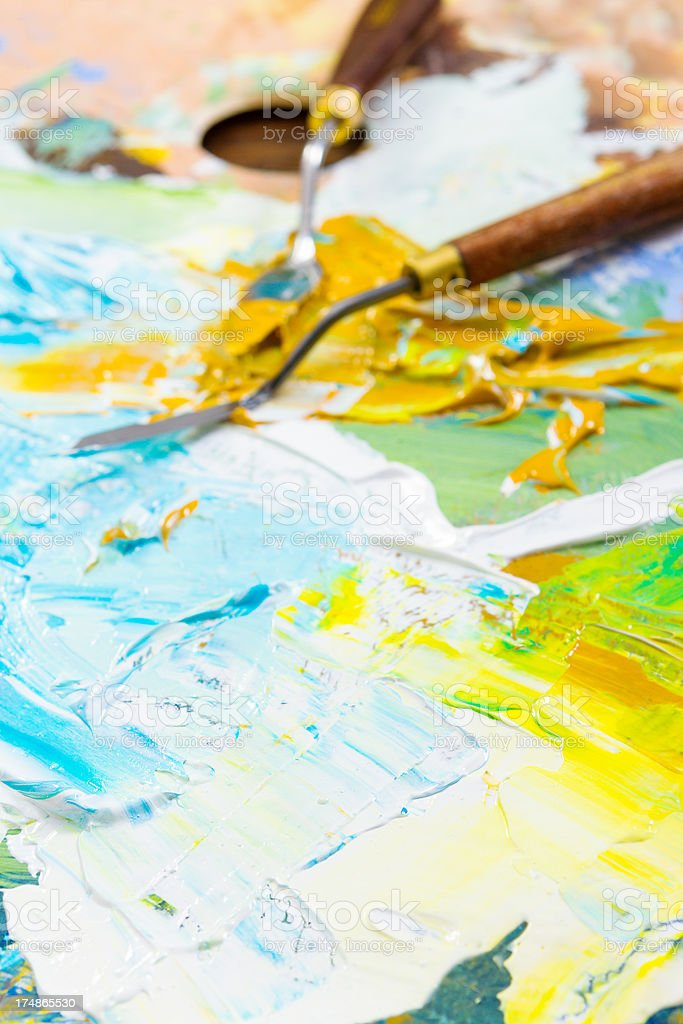 knives and colorful paint on an artist palette stock photo