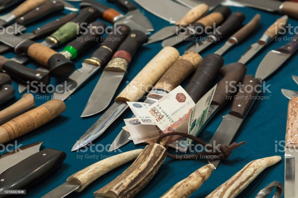 Knives hunting and Russian money rubles. Purchase of cutting weapons. stock photo