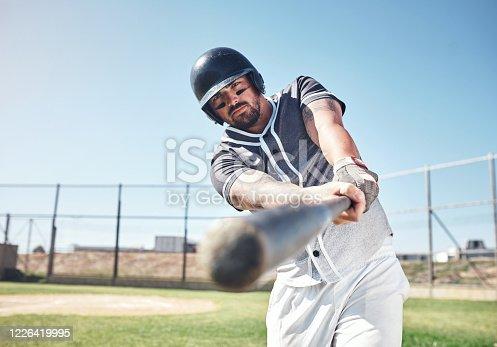 Shot of a young man swinging his bat at a baseball game
