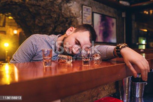 Young caucasian drunk man sleeping in bar.