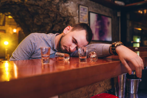 Knock out on bar counter Young caucasian drunk man sleeping in bar. drunk stock pictures, royalty-free photos & images