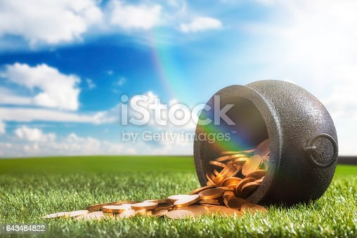 Low angle of a black wrought iron kettle pot that has been knocked over spilling it's gold coins onto the grass, with sun flare and  rainbow. Mythology says it is the secret hiding place of an Irish Leprechaun's pot of gold, some even say he is tricky.