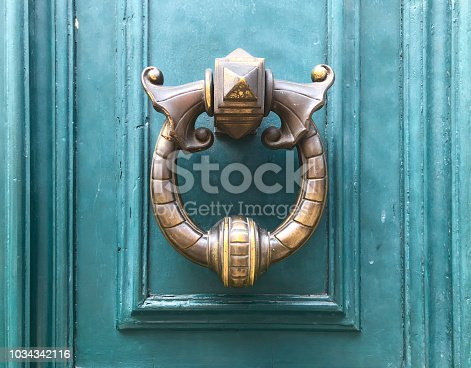 Weathered brass door knocker on teal painted door in Paris France.