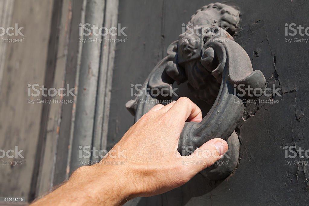 Knocking old black door with metal ring knocker stock photo