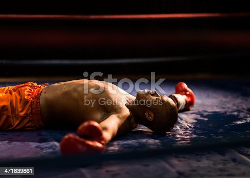 Boxer knocked out laying on the mat with his arms stretched out.