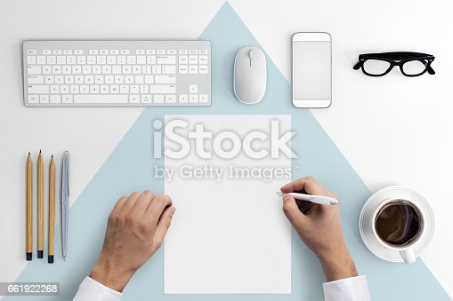 Direct view at hands writing on a blank paper .Office desk with pc keyboard, smartphone, coffee, notebook, pencils, white and blue desk pattern. copy space. hipster template