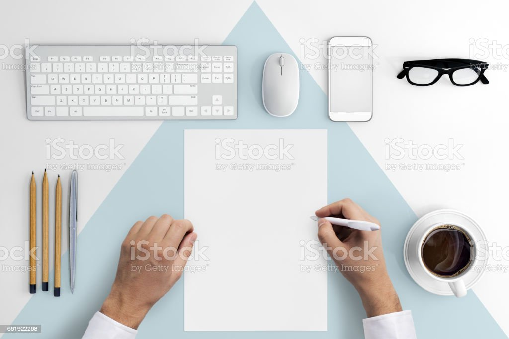 Knolling hands writing on a blank paper stock photo