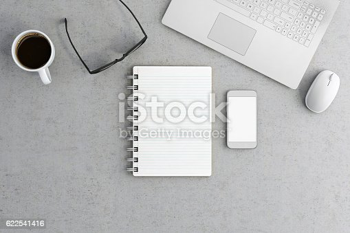 Knolling concept, overhead POV view of an office desk, with a blank notepad in the center,  with smart phone, a laptop and a coffee cup. Horizontal composition render. Ideal for embedding additional design