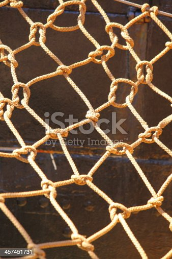 Knot rope netting orange safety net on ship grunge metal background
