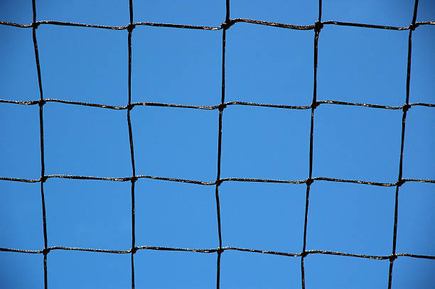 Knotted grid like a chain-link fence against cloudless blue sky  ensnare stock pictures, royalty-free photos & images