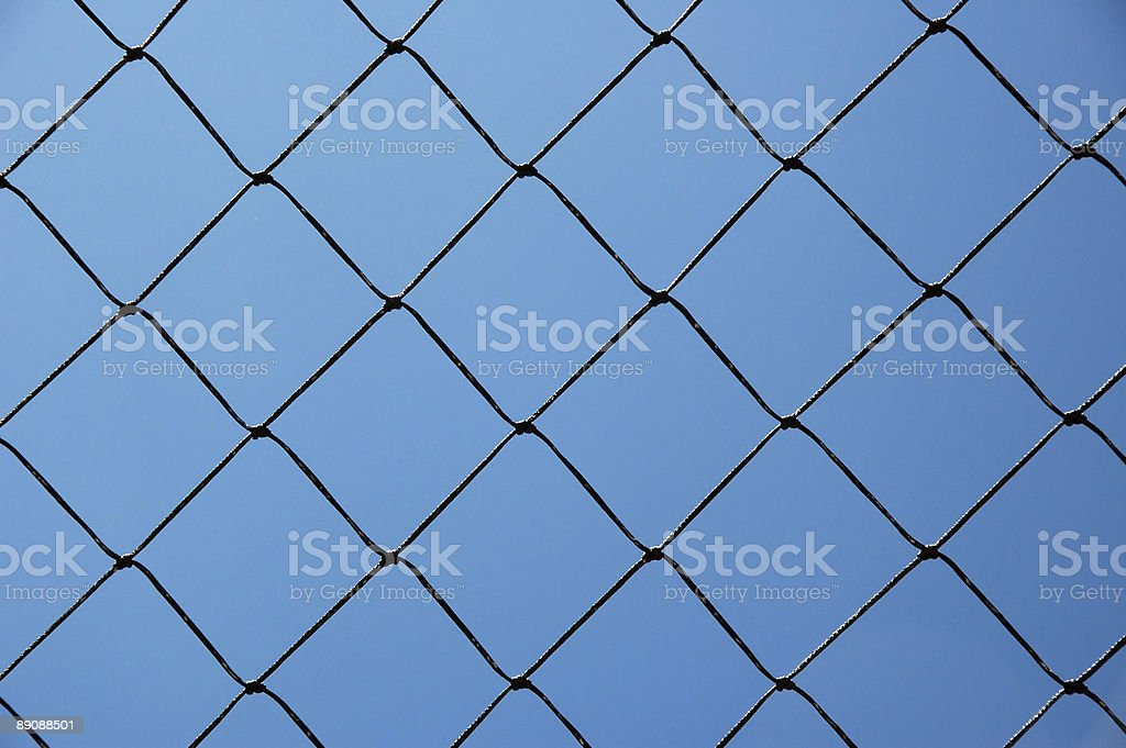 Knotted grid like chain-link fence against cloudless blue sky stock photo